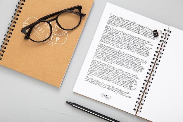 Flache lage der schreibtischoberfläche mit notizbüchern und brille