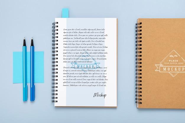 Flache lage der schreibtischoberfläche mit notizbüchern und stiften