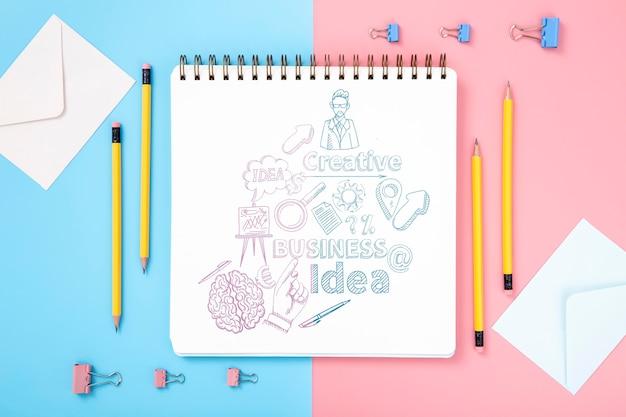 Flache lage der schreibtischoberfläche mit stiften und notizbuch