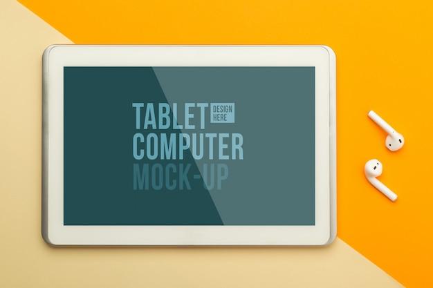 Flache lage, draufsicht auf orange bürotisch schreibtisch mit tablet-computer-modellvorlage für ihr design und drahtlose kopfhörer. moderner arbeitsraum