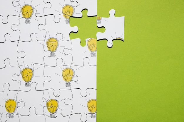 Flache lageanordnung mit puzzlespiel auf grünem hintergrund