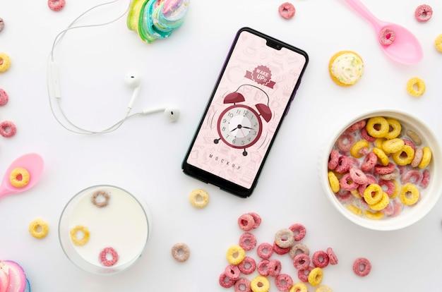 Flaches morgenfrühstück mit smartphone-modell