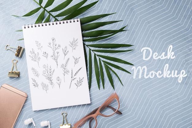 Flaches notizbuchmodell und briefpapier in der nähe von gläsern