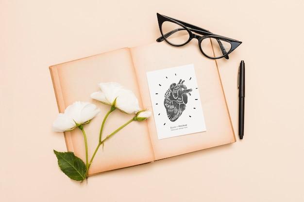 Flaches offenes buch mit rosen und gläsern