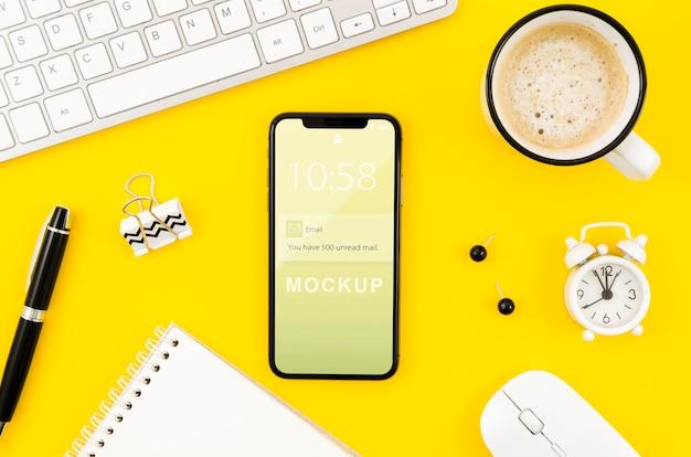 Flaches smartphone-modell auf dem schreibtisch mit kaffee