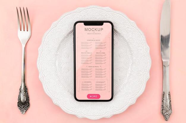 Flaches smartphone-modell auf teller legen