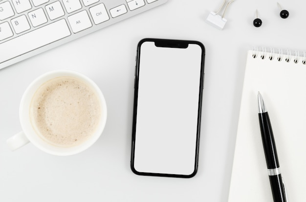 Flaches smartphone-modell mit leerer tasse auf dem schreibtisch