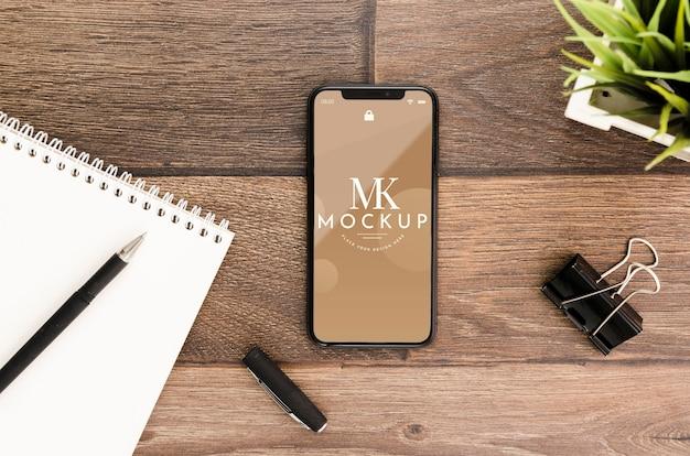 Flaches smartphone-modell mit motepad auf dem schreibtisch
