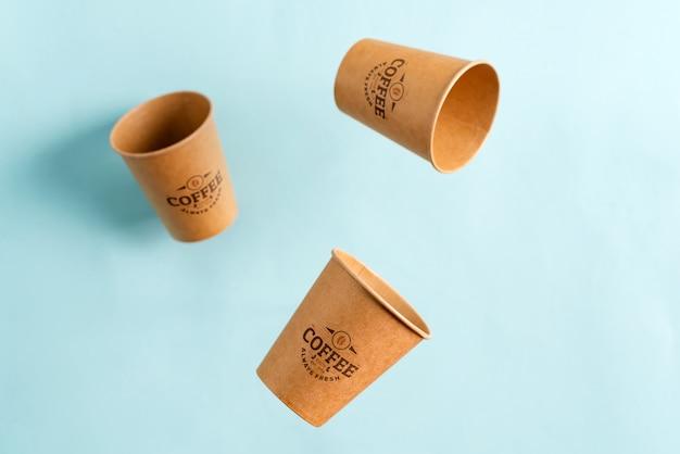 Fliegende umweltfreundliche papier-einweg-modellbecher über pastellblauem hintergrund. kein verlust