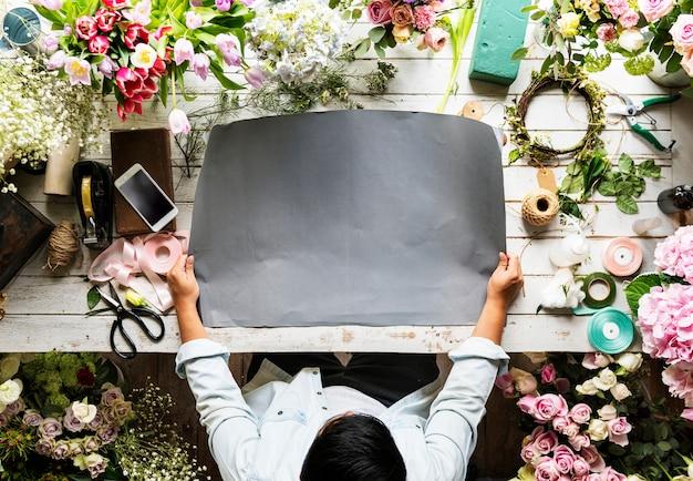 Florist, der leeres design-raum-papier auf holztisch zeigt