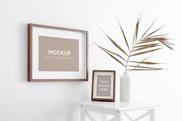Foto- oder kunstwerkrahmenmodell auf weißer wand mit trockenen palmblattdekorationen in der vase