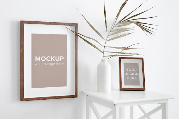 Foto- oder kunstwerkrahmenmodell auf weißer wand und möbeln mit trockenem palmblatt in vase