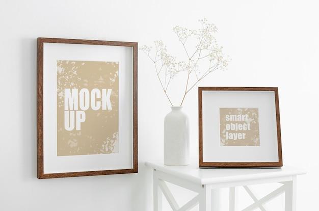 Foto- oder kunstwerkrahmenmodell auf weißer wand und möbeln mit trockener schleierkrautpflanze in vase