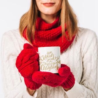 Frau, die bechermodell mit weihnachtskonzept hält