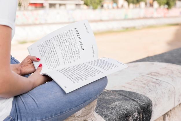 Frau, die buch auf straße liest
