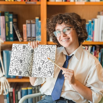Frau, die buchmodell in der bibliothek hält