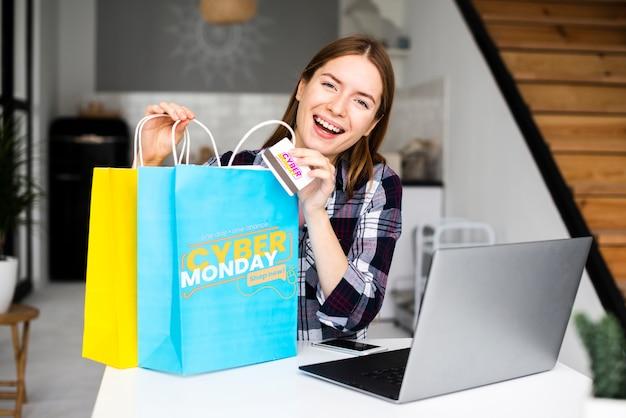 Frau, die cybermontag-papiertüten und eine kreditkarte hält