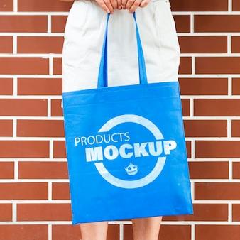 Frau, die ein einfaches blaues taschenmodell hält