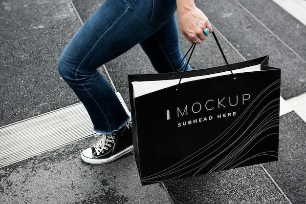 Frau, die ein einkaufstaschemodell trägt