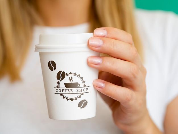 Frau, die ein kaffeepapiertassenmodell hochhält