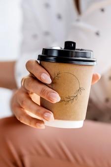Frau, die ein kaffeetassenmodell hält