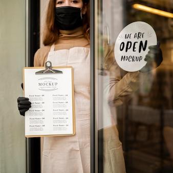 Frau, die ein restaurantmenü-modell auf zwischenablage hält