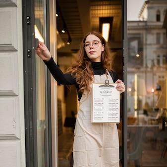 Frau, die ein restaurantmenü-modell hält