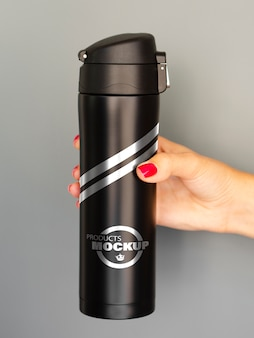 Frau, die ein schwarzes thermosflaschenmodell hält