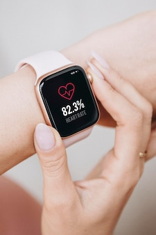 Frau, die ein smartwatch-modell trägt, um ihre herzfrequenz zu überprüfen