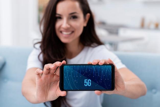 Frau, die ein telefon mit 5g konzeptmodell hält