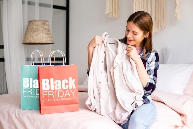Frau, die ein tuch von einer schwarzen freitag-tasche nimmt