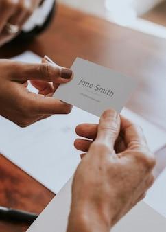 Frau, die ein visitenkartenmodell überreicht