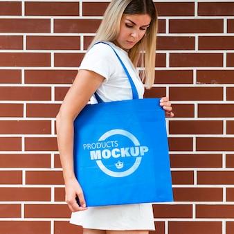 Frau, die eine einfache blaue tasche hält