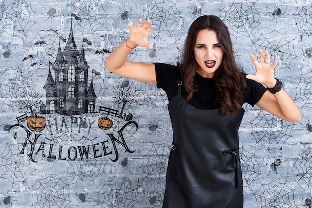 Frau, die eine furchtsame geste für halloween zeigt