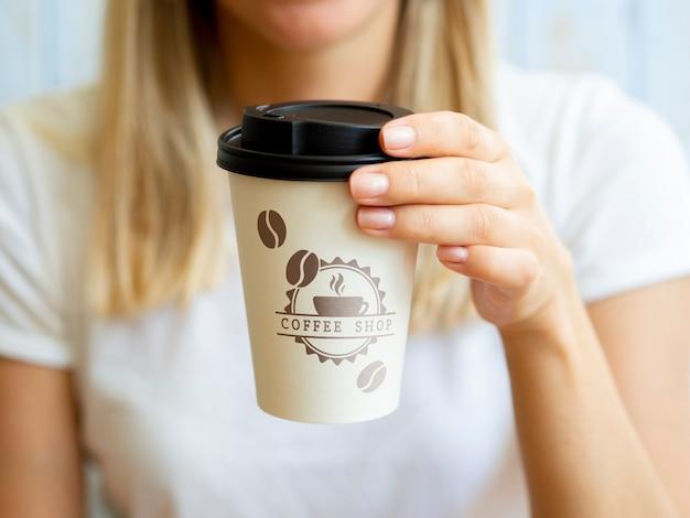 Frau, die eine kaffeepapiertasse hält