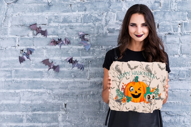 Frau, die eine karte mit geschnitztem kürbis für halloween hält