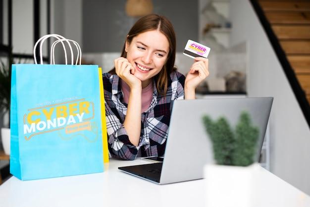 Frau, die eine kreditkarte hält und auf laptop schaut