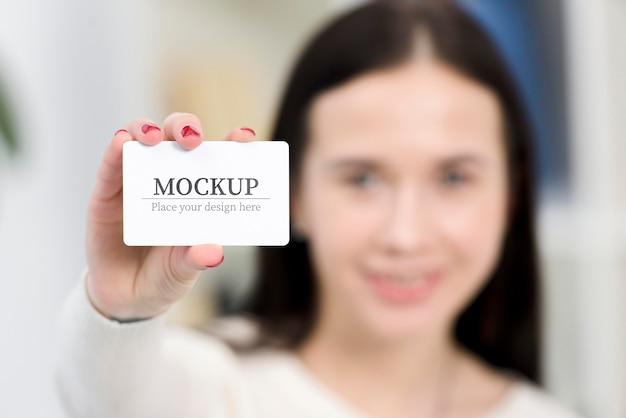 Frau, die eine modell-visitenkarte hält