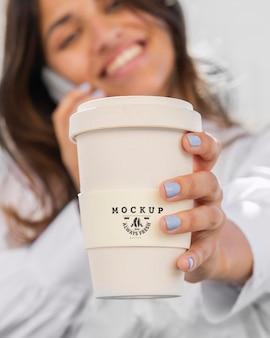 Frau, die eine nachgebildete tasse kaffee hält