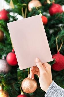 Frau, die eine rosa weihnachtskarte vor einem weihnachtsbaummodell hält