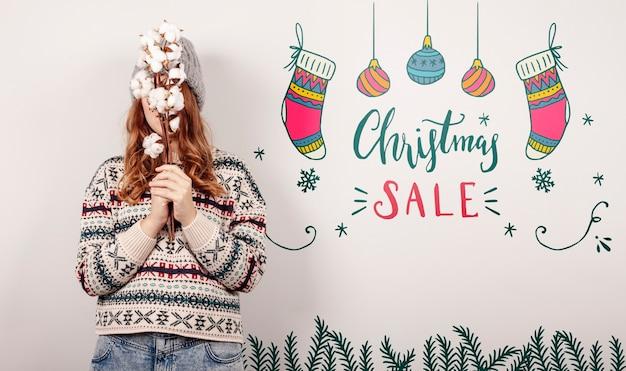 Frau, die eine weihnachtsstrickjacke und weihnachtsverkaufsangebote trägt