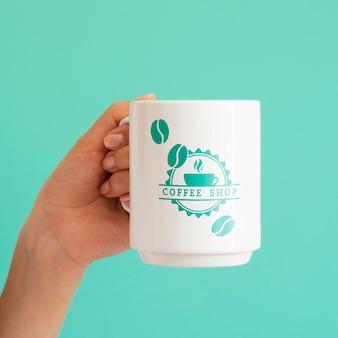 Frau, die eine weiße kaffeetasse hochhält