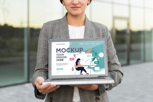 Frau, die einen modell-laptop für arbeit hält