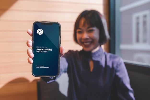 Frau, die ihr smartphone-bildschirmmodell im café zeigt