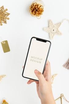 Frau, die ihr telefon über goldweihnachtsschmuckmodell hält