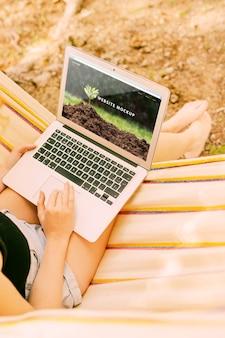 Frau, die laptopmodell in der natur verwendet