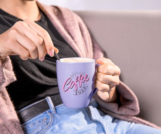 Frau, die lila kaffeetasse hält