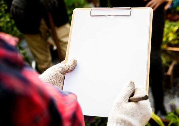 Frau, die liste auf klemmbrett auf organisches neues agrarprodukt überprüft