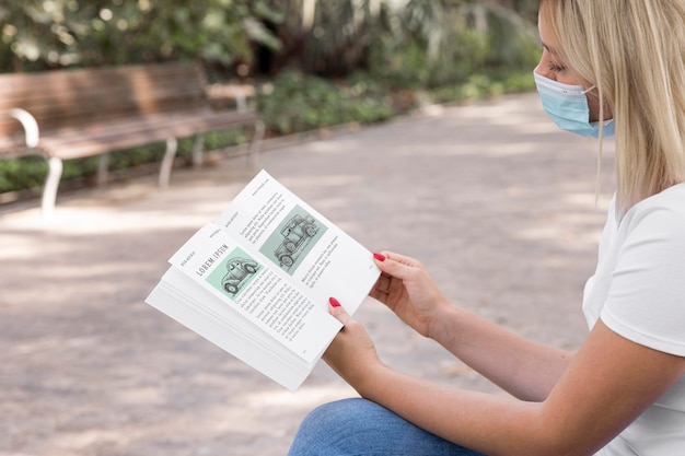Frau, die maske auf straßenlesebuch trägt