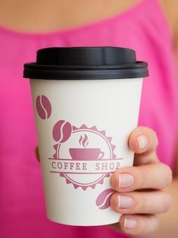 Frau, die papierkaffeetassenmodell hält
